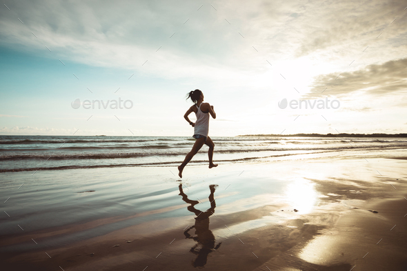 Woman running on sunset beach - Stock Photo - Images