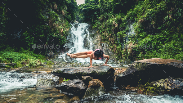 Woman practice yoga infront of waterfall - Stock Photo - Images