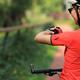 Woman biker looking at her smartwatch outdoors - PhotoDune Item for Sale