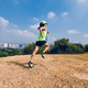 Woman running on dirt mountain trail with modern city in the distance - PhotoDune Item for Sale
