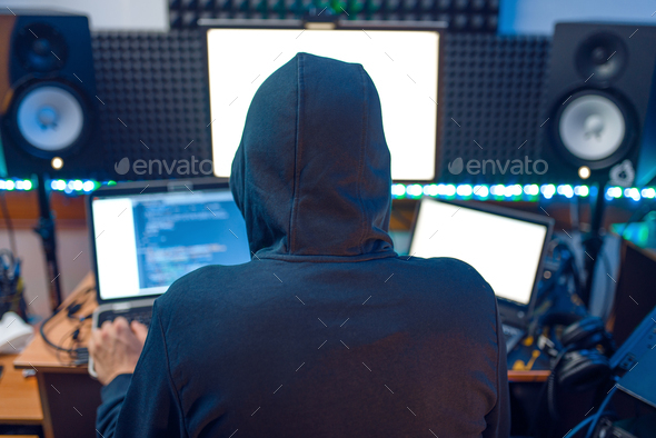 Hacker in the hood sitting at laptop, back view - Stock Photo - Images