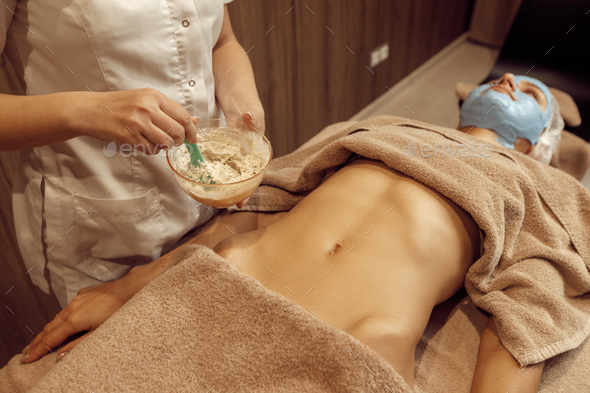 Female masseur applies cream on stomach of woman - Stock Photo - Images