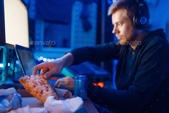 Male gamer eating pizza, night tournament - Stock Photo - Images