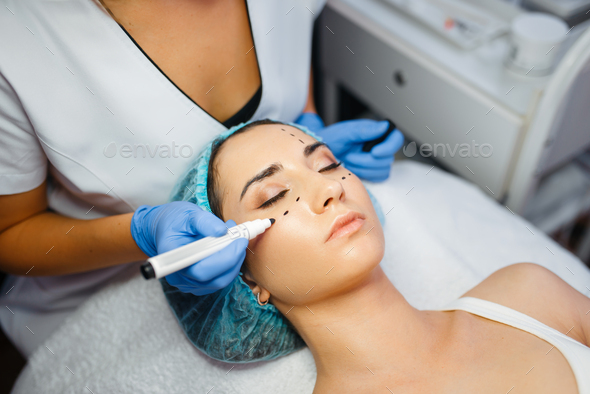 Cosmetician with marker puts dotted lines on face - Stock Photo - Images