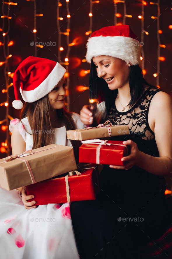 Mother and daughter with Christmas presents.Christmas gifts against bright lighting garland - Stock Photo - Images