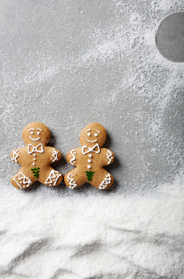 Two gingerbread men having a walk on snowy street sunny day - Stock Photo - Images