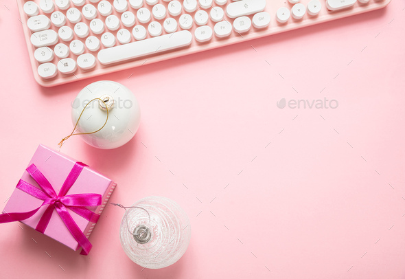 Christmas balls, gift and computer keyboard against pink background - Stock Photo - Images