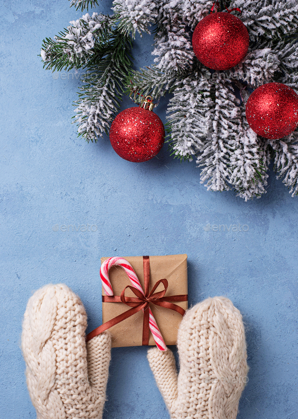 Hands in mittens holding Christmas gift box - Stock Photo - Images