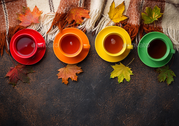 Colorful cups of tea, plaid and leaves - Stock Photo - Images