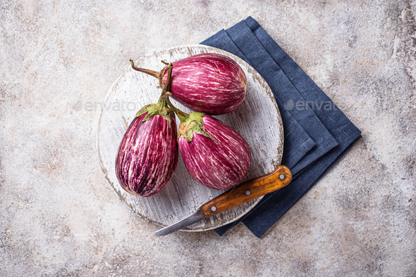 Fresh striped purple aubergines on light background - Stock Photo - Images