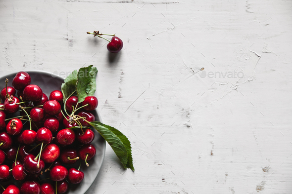sweet cherries in a plate on an old white background, healthy food, fruits - Stock Photo - Images
