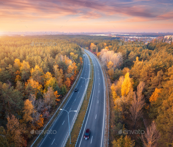 Aerial view of road in beautiful autumn forest at sunset - Stock Photo - Images