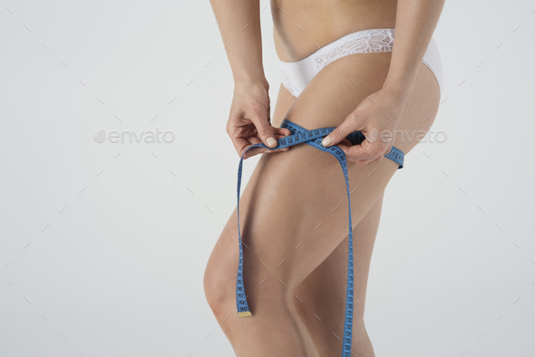 Close up of woman's legs with tape measure - Stock Photo - Images