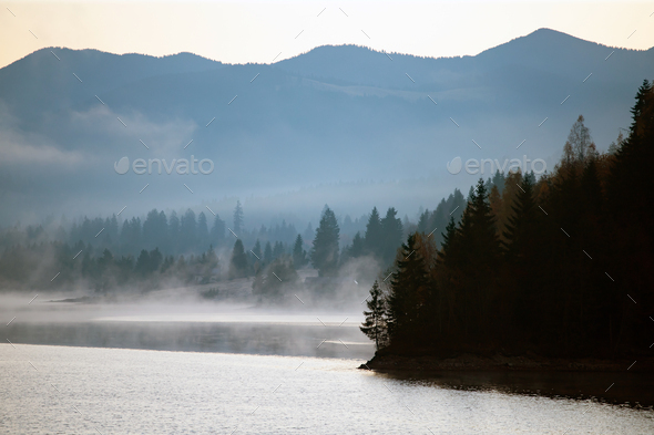 Lovely autumnal landscape with fog over the lake. - Stock Photo - Images