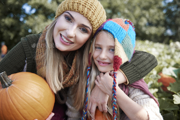Portrait of mom and daughter with pumpkin - Stock Photo - Images