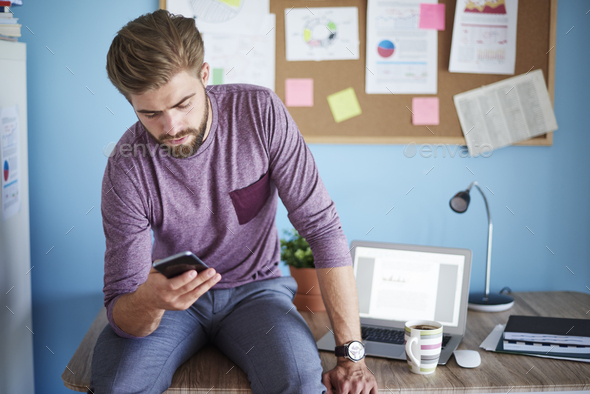 Man sitting on desk and having a rest - Stock Photo - Images
