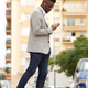 young african businessman walking in the city with mobile phone and earphones - PhotoDune Item for Sale