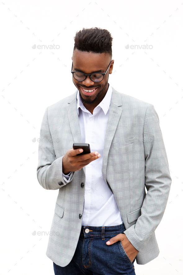 smiling young businessman looking at mobile phone - Stock Photo - Images