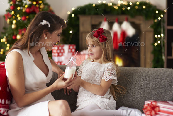 Mother passing bottle of milk to daughter - Stock Photo - Images