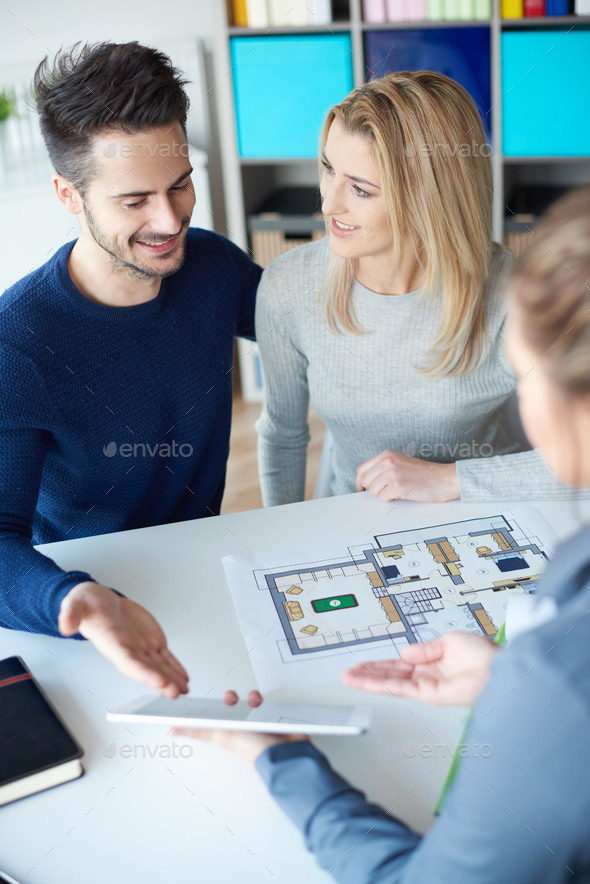 Couple and saleswoman looking at digital tablet - Stock Photo - Images