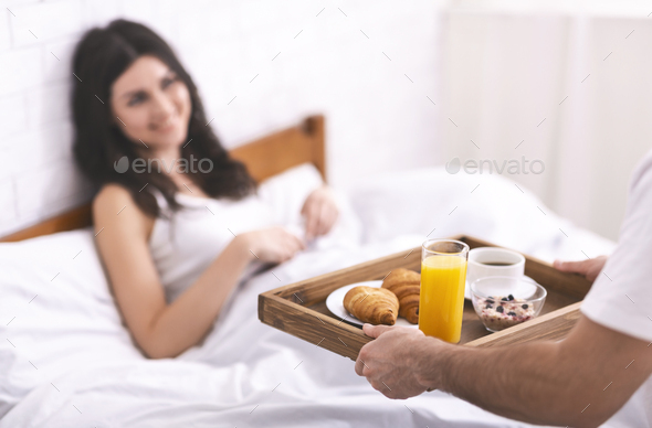 Lovely boyfriend bring breakfast to his girlfriend in morning - Stock Photo - Images