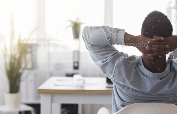 Black worker sitting in office with hands behind his head - Stock Photo - Images
