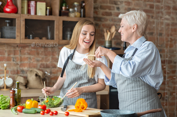 Young woman helping her old mother with dinner - Stock Photo - Images
