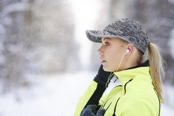 Side view of female athlete listening to music - Stock Photo - Images