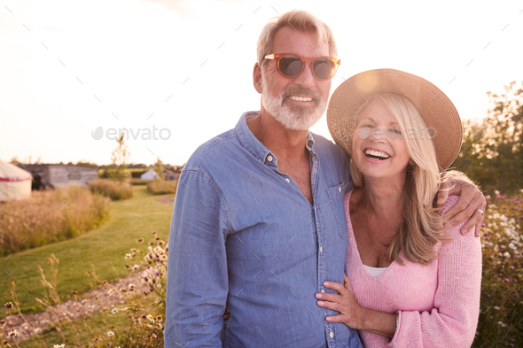 Portrait Of Loving Mature Couple In Countryside Hugging Against Flaring Sun - Stock Photo - Images