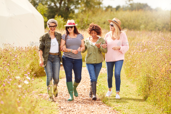 Group Of Mature Female Friends Walking Along Path Through Yurt Campsite - Stock Photo - Images