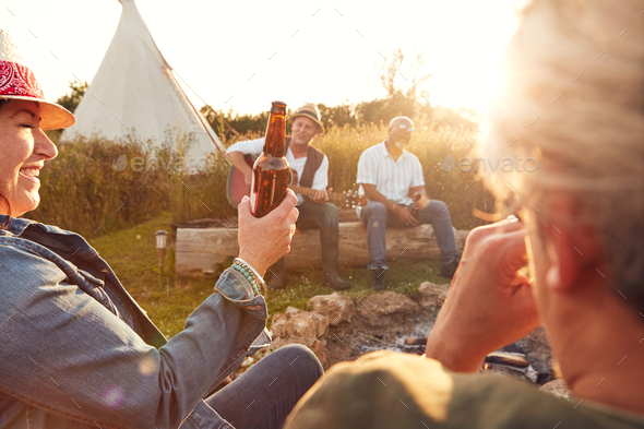 Group Of Mature Friends Sitting Around Fire As They Drink And Sing Songs At Outdoor Campsite - Stock Photo - Images