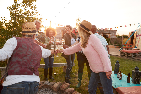 Group Of Mature Friends Sitting Around Fire And Making A Toast At Outdoor Campsite Bar - Stock Photo - Images