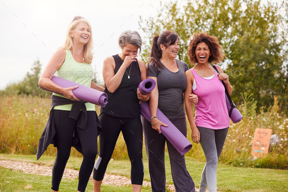 Group Of Mature Female Friends On Outdoor Yoga Retreat Walking Along Path Through Campsite - Stock Photo - Images