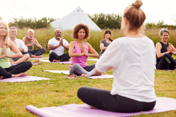 Female Teacher Leading Group Of Mature Men And Women In Class At Outdoor Yoga Retreat - Stock Photo - Images
