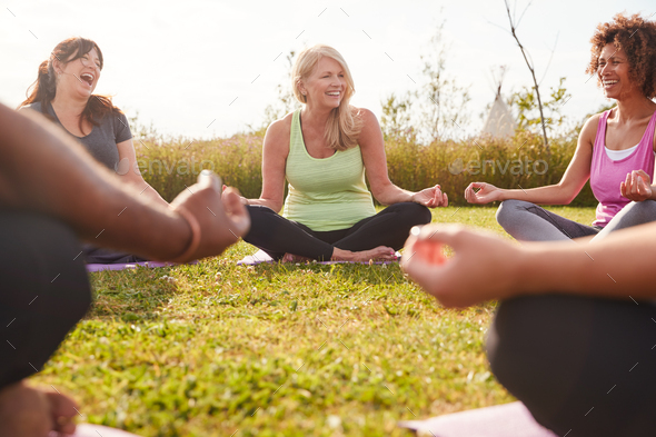 Group Of Mature Men And Women In Class At Outdoor Yoga Retreat Sitting Circle Meditating - Stock Photo - Images