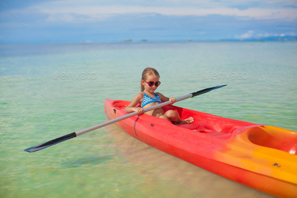 Little adorable girl rowing a boat in blue clear sea - Stock Photo - Images