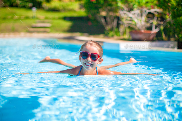 Little adorable happy girl swims in the swimming pool - Stock Photo - Images