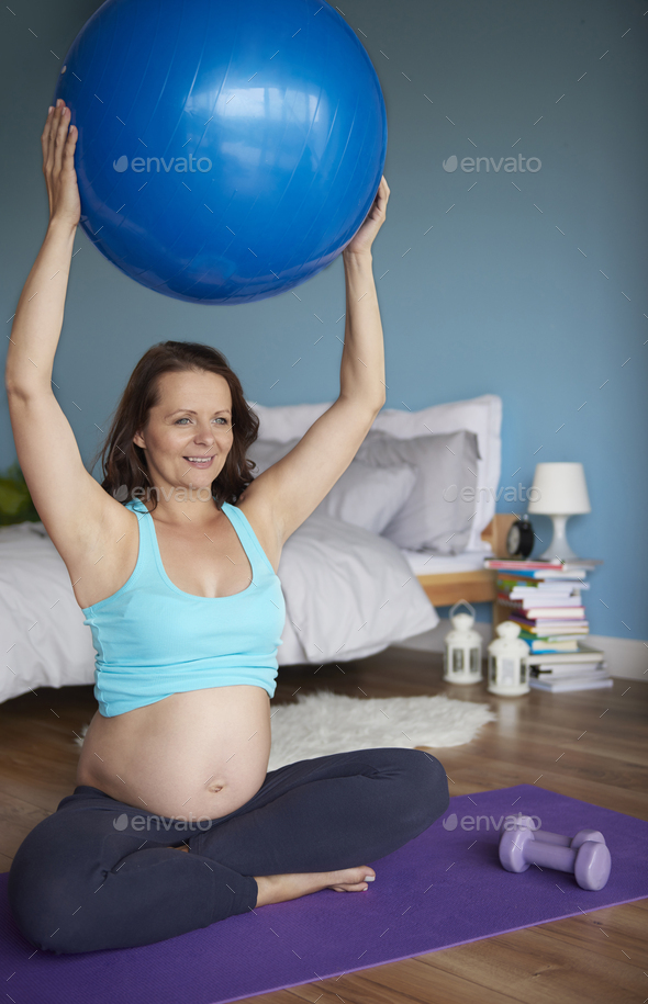 Hands raised with exercise ball - Stock Photo - Images
