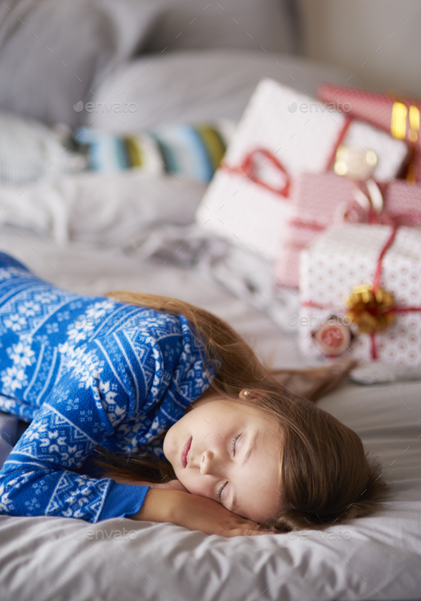 Sleeping girl in Christmas morning - Stock Photo - Images