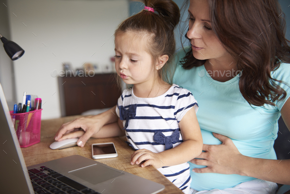 Mother showing daughter how to use computer - Stock Photo - Images