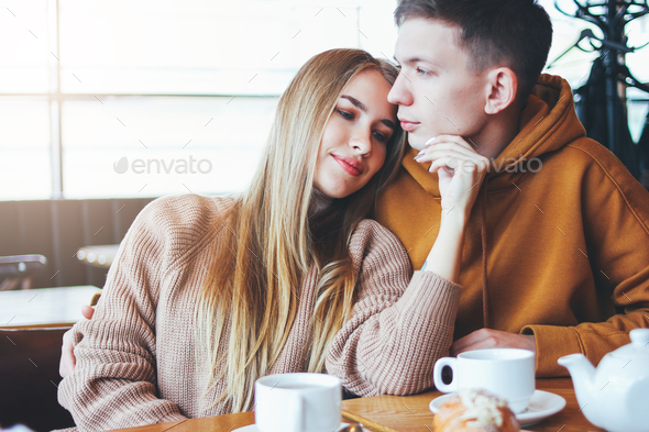 Young couple dressed warm casual clothing sitting at cafe together - Stock Photo - Images