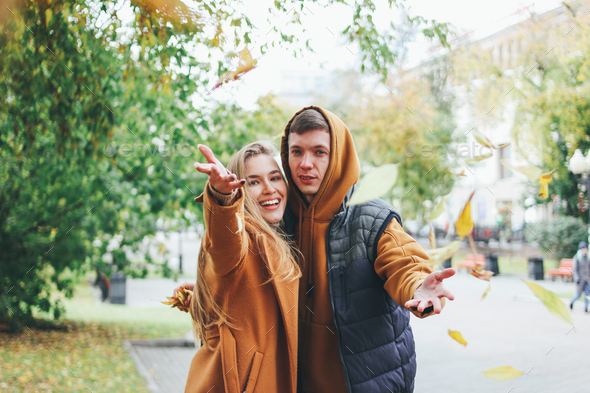 Happy young couple dressed in casual style walking and throws leaves at camera - Stock Photo - Images