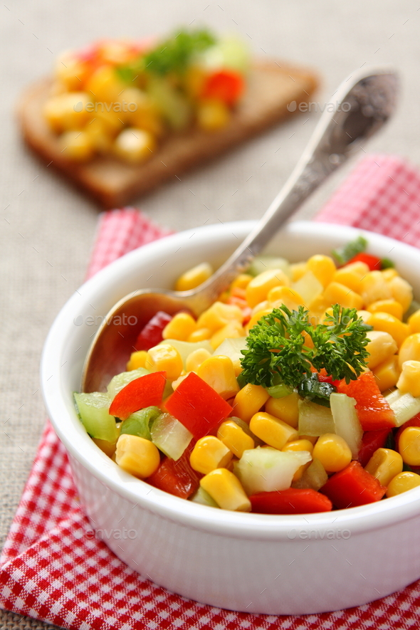 Homemade corn salsa in white bowl with spoon - Stock Photo - Images
