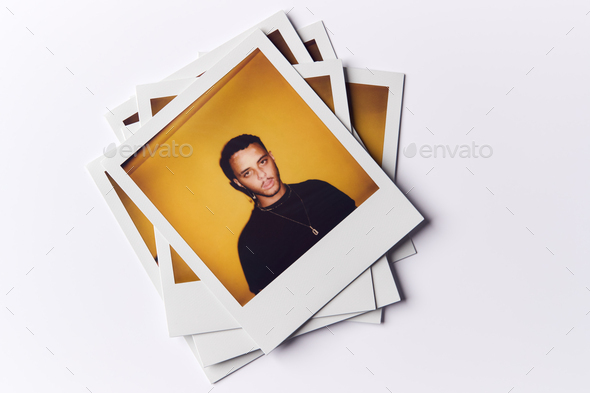 Stack Of Instant Film Photos From Modeling Casting In Studio With Shot Of Young Man On Top - Stock Photo - Images