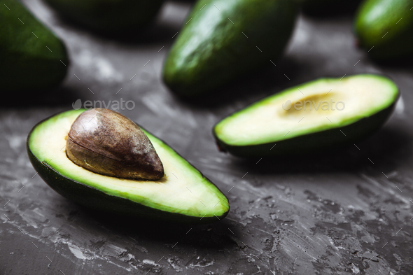 Fresh avocado on dark background. Vegetarian food concept. Top view - Stock Photo - Images