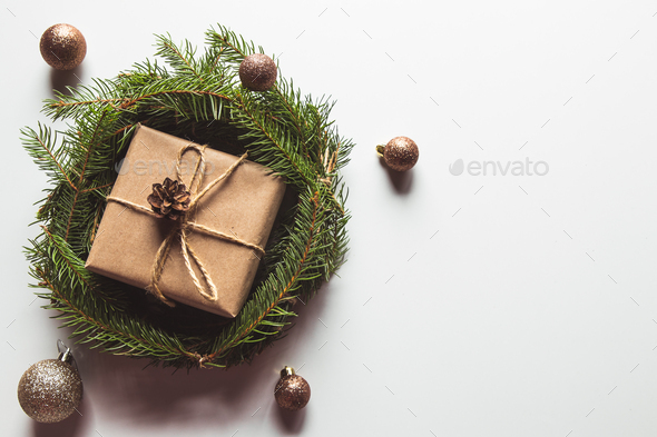 Gift in craft paper in a wreath of Christmas trees. Christmas mood, New Year, On white background - Stock Photo - Images