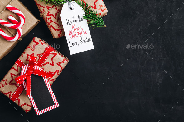 Christmas background with fir branches and a gift box with a red bow on a dark concrete background. - Stock Photo - Images