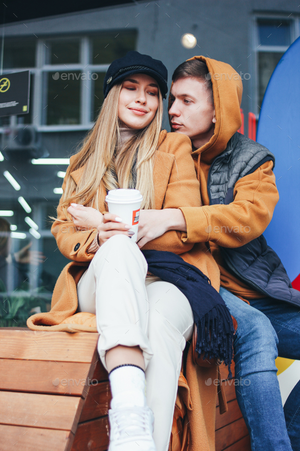 Happy young couple dressed in casual style walking on city street in cold season - Stock Photo - Images