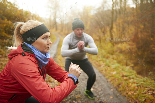 Athletic couple doing squats among forest - Stock Photo - Images