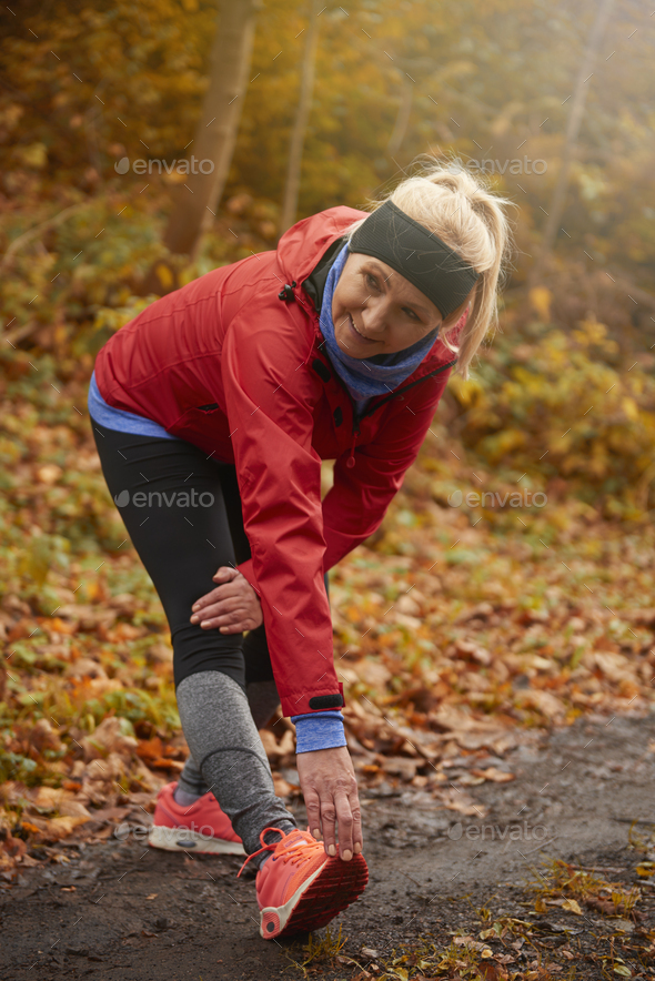 Senior woman stretching in public park - Stock Photo - Images